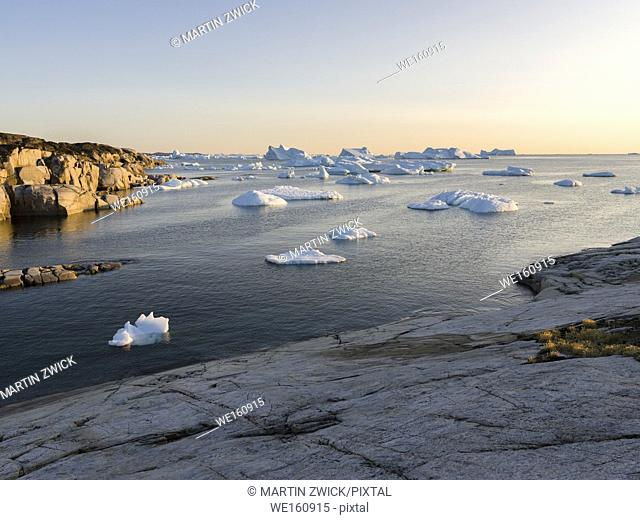 Coastal landscape with Icebergs. The Inuit village Oqaatsut (once called Rodebay) located in the Disko Bay. America, North America, Greenland, Denmark