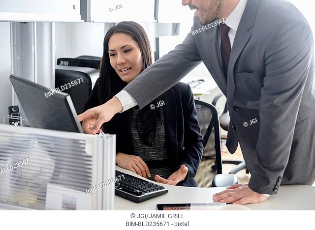 Business people talking in office using computer