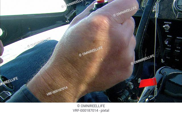 CU Male pilot hand holding joystick in light aircraft cockpit / Howick, KwaZulu-Natal Province, South Africa