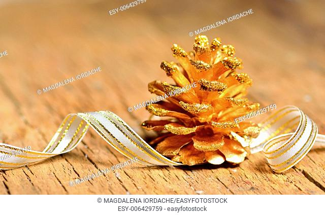 Golden pine cone on old wooden background