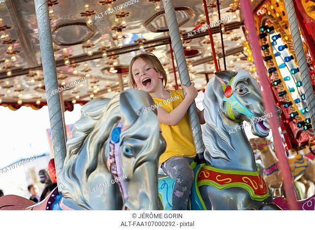 Little girl riding on carousel