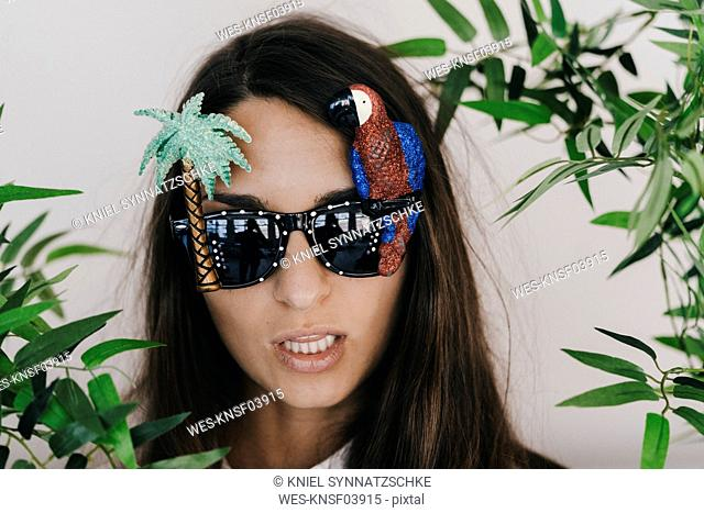 Young woman wearing exotic sunglasses with palm tree and parrot
