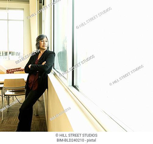 Portrait of Filipino woman leaning near window