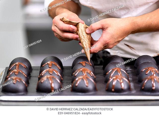Professional confectioner making chocolate sweets at confectionery shop