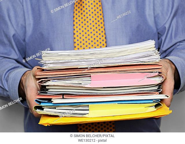 Overworked Businessman Carrying a Stack of Paperwork. Close Up