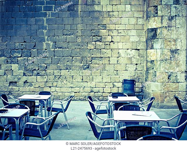 Tables and chairs, old wall background. Plaça del Rei, Gothic quarter, Barcelona, Catalonia, Spain