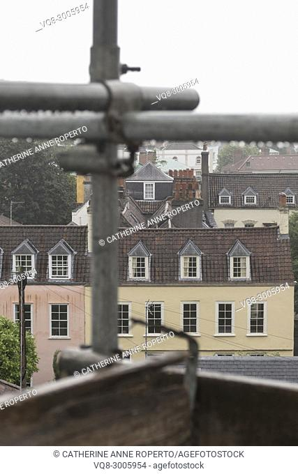 Metal scaffolding poles after the rain, looking out over the historic rooftops and chimneys of Hotwells, Bristol, England