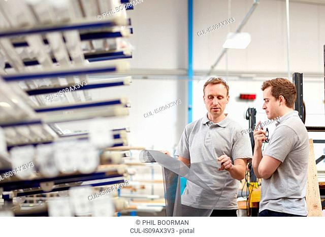 Manager examining fabric with worker in roller blind factory