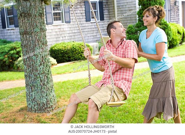 Mature woman pushing a mature man on a rope swing and smiling