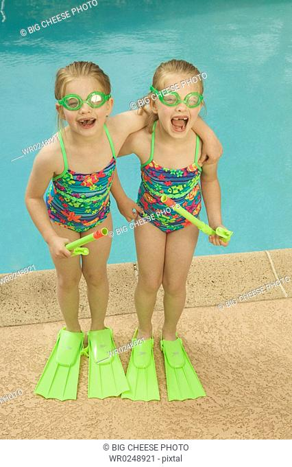 Twin girls standing poolside