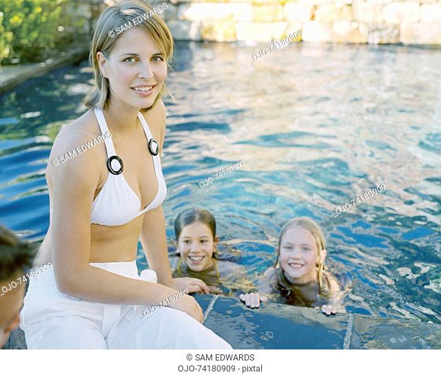 Two girls swimming outdoors with mother