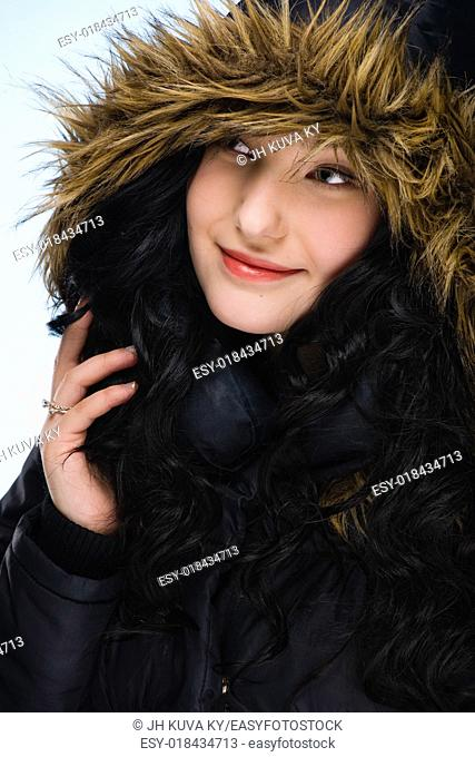 Beautiful girl wearing hood, light blue background, vertical format