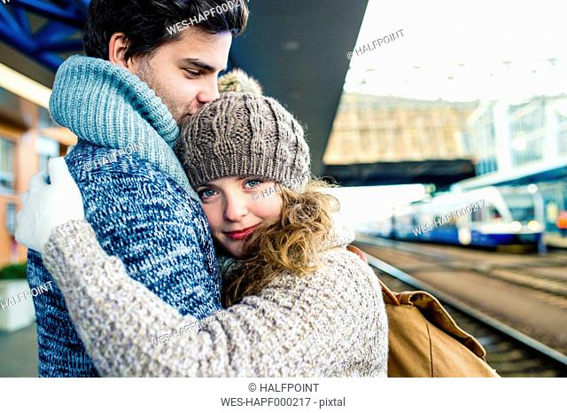 Young couple embracing on station platform