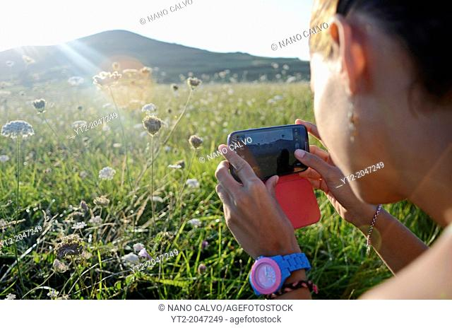 Young woman takes photos of nature with her mobile phone