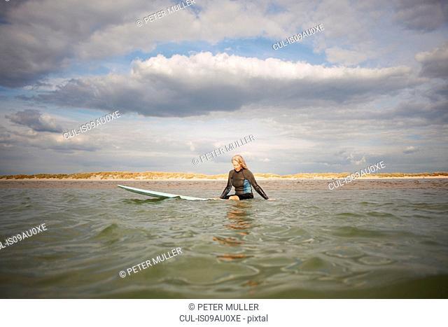 Senior woman sitting on surfboard in sea