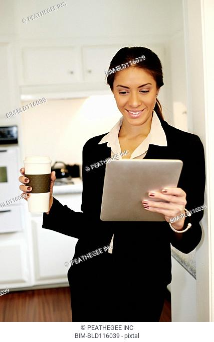 Mixed race businesswoman using tablet computer in kitchen