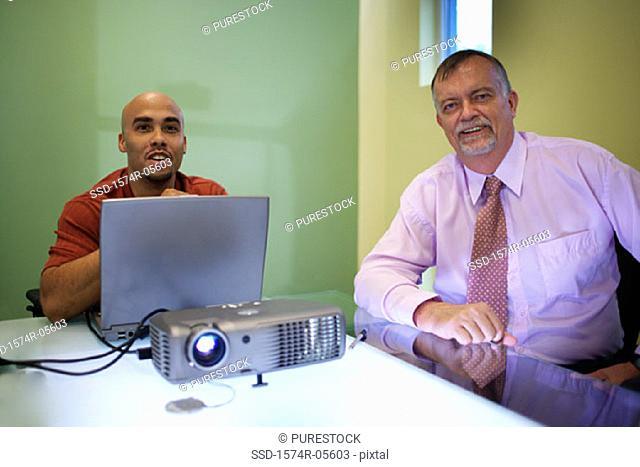 Two businessmen smiling during a slide presentation