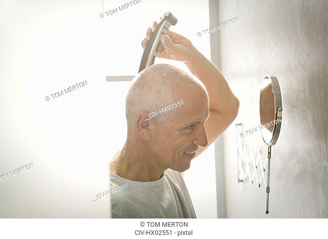 Mature man shaving head with electric razor in bathroom
