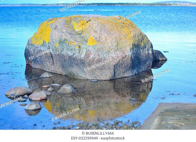 round rock reflecting in silence blue water