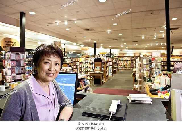 Portrait of an Asian American female owner of a bookstore at a computer at the front desk of the store