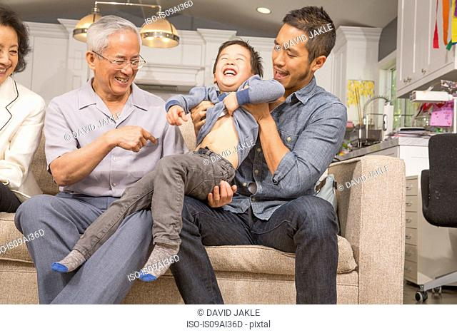 Three generation family playing with young boy on sofa