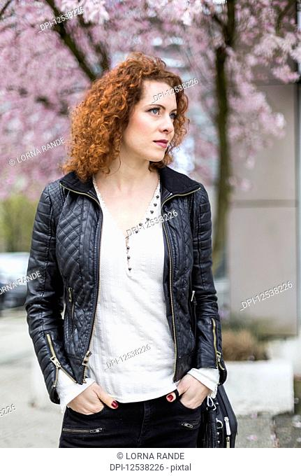 A woman with red, curly hair walking outdoors in springtime; North Vancouver, British Columbia, Canada