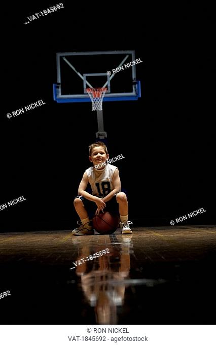 Young boy sitting on basketball court