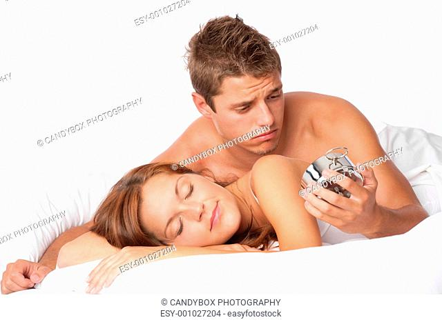 Young couple oversleep, wake up in bed