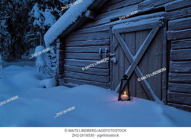 Old barn with lantern burning outside at the door, with snow on the ground and frost on the door, at time of dusk, Gällivare, Swedish Lapland, Sweden