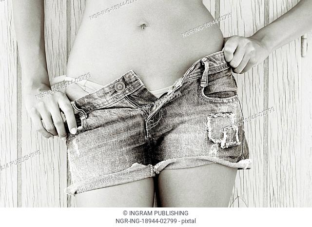 Close up of a woman in jeans texas shorts and pink bikini