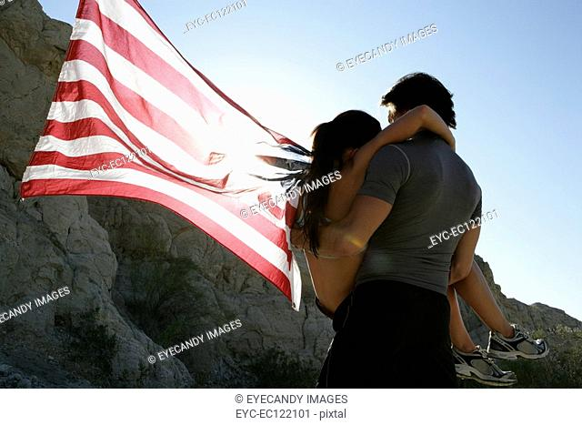 Young man carrying woman holding flag
