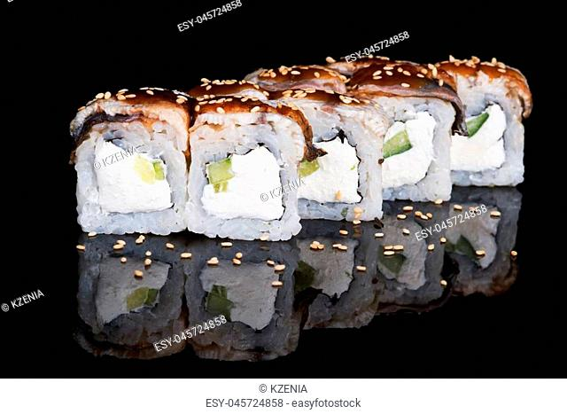 Sushi rolls with eel, cucumber and soft cheese on black background