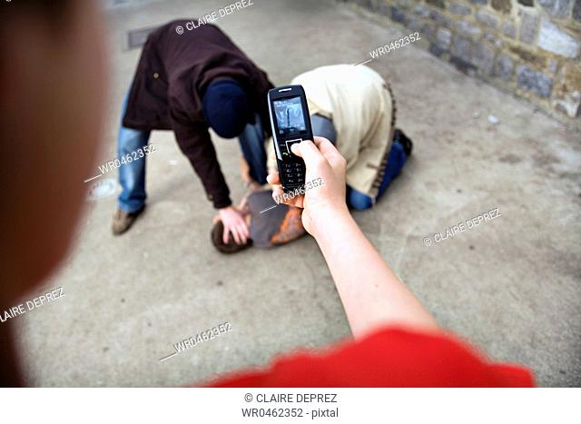 Close-up of a teenage boy taking a photograph of three teenage boys fighting
