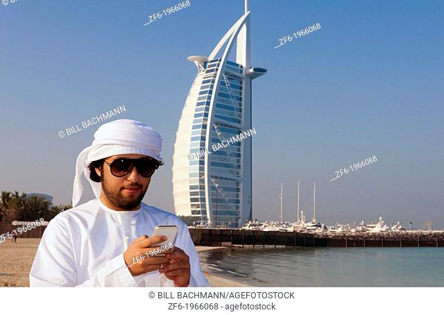 Emirate arab man with cell phone texting in front of Worlds only 7 star hotel in Dubai UAE called the Burj Al Arab with luxury and water at beach in United Arab...