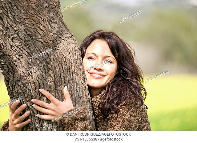 Pretty brunette woman embracing tree