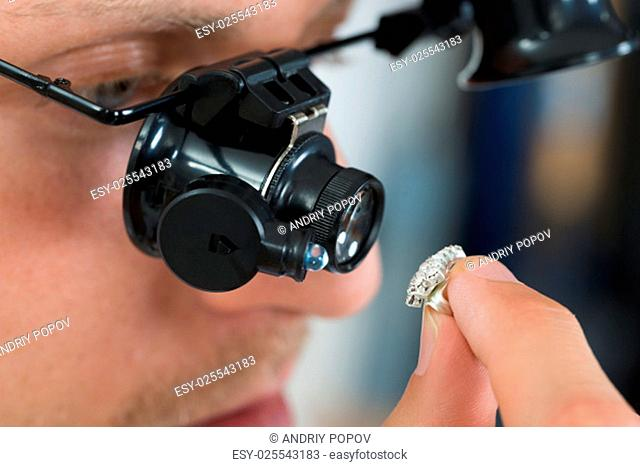 Close-up Of Jeweler Looking Ring Through Magnifying Loupe