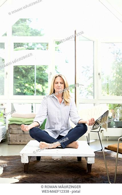 Blond woman sitting on coffee table, meditating