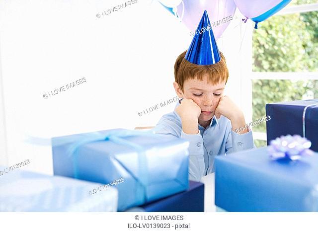 boy looking sad at birthday party