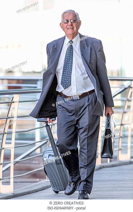 Smiling senior businessman leaving hotel with wheeled suitcase