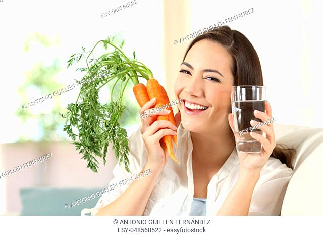 Happy woman showing healthy raw carrots and water glass sitting on a couch in the living room at home