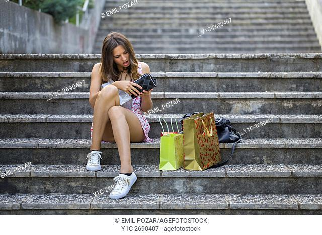 Young woman shopper checking money wallet surprised shocked shock sitting on staircase