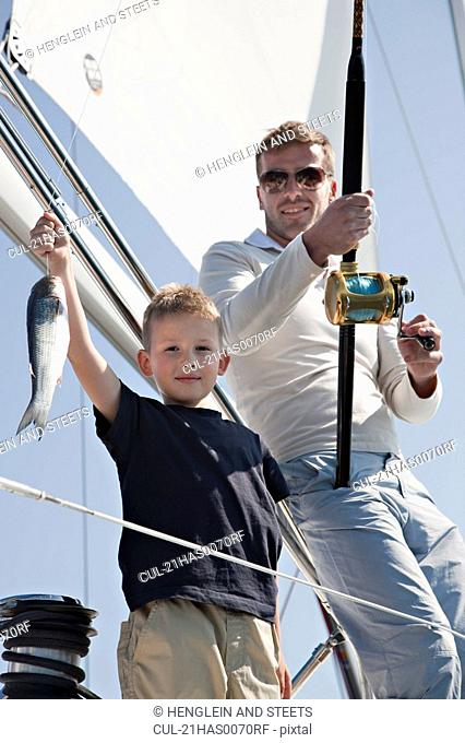 Father and son fishing on yacht