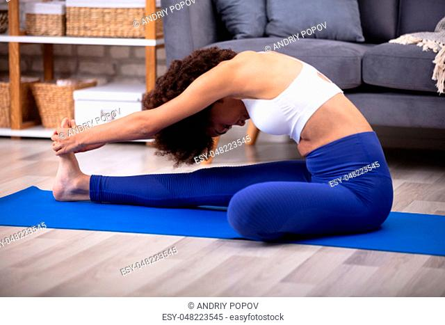 Fit Woman In Curly Hair Stretching Her Leg Sitting On Blue Exercise Mat At Home