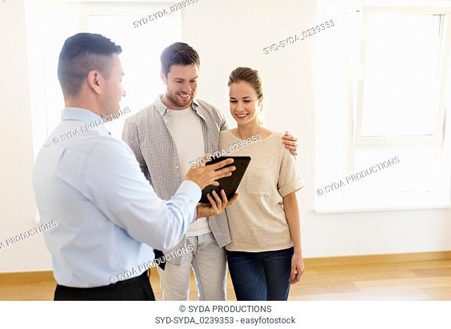 couple and realtor with tablet pc at new home
