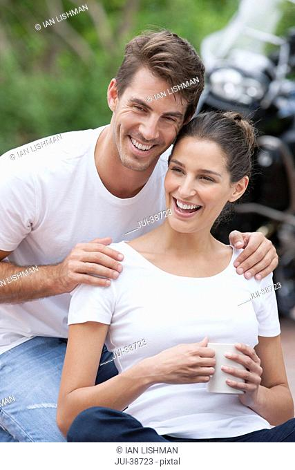Laughing couple drinking coffee with motorcycle in background