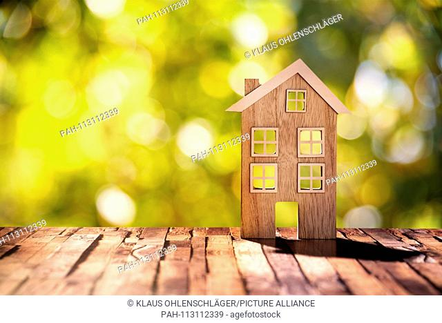Wooden house on wooden floor in front of nature background with bokeh | usage worldwide