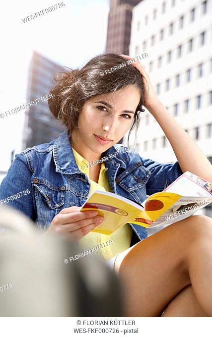 Germany, Berlin, portrait of young woman on city trip sitting at Potsdam Square with guidebook