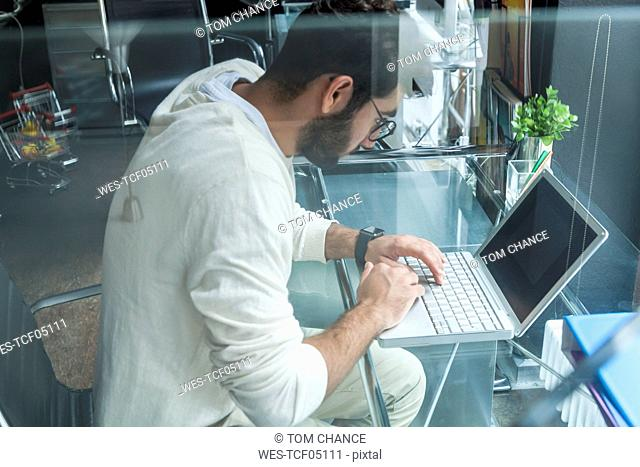 Young man working with laptop at desk in a modern office