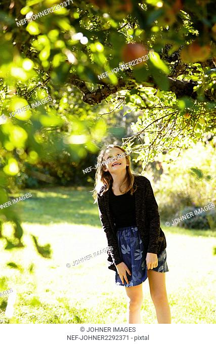 Blond girl in apple orchard