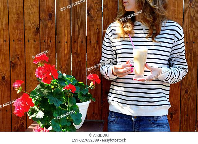 Glass Latte in woman hands and pot with blooming red flowers on background of wooden fence